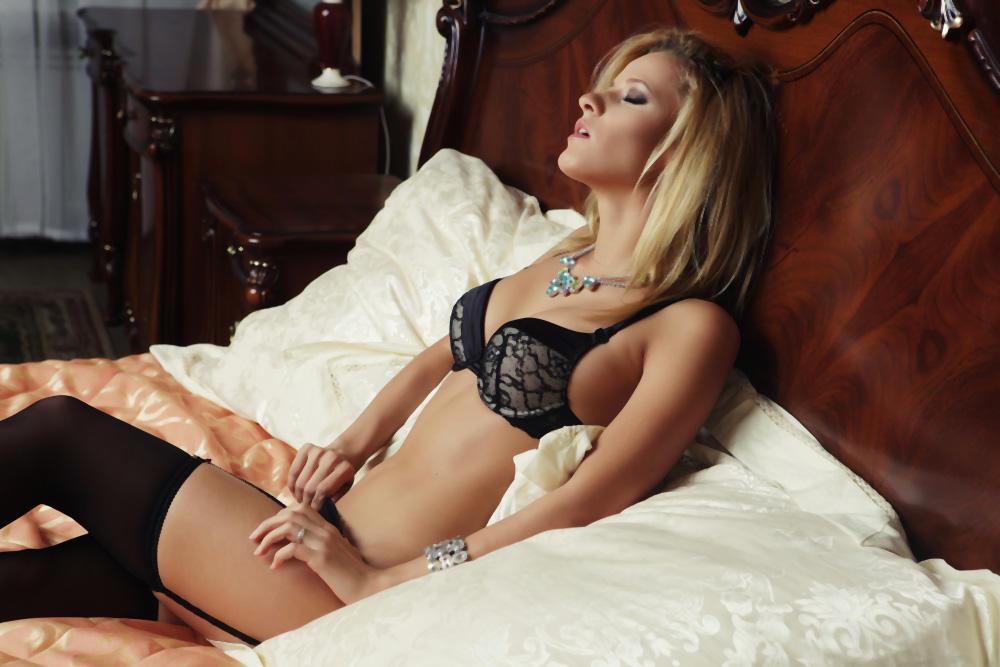 Zanosna žena sa halterima sedi u krevetu